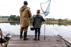 Father and son fishing with rod and net. On wooden pier at lake Royalty Free Stock Photography