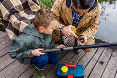 Father and son with fishing rod. On wooden pier at lake Stock Photography