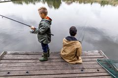 Father and son fishing with rods. Father and son fishing together with rods on wooden pier at lake Royalty Free Stock Photography