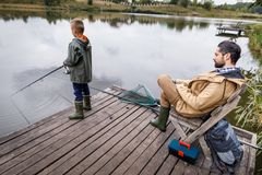 Father and son fishing with rods. On wooden pier at lake Stock Photos