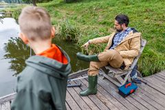 Father and son fishing with rods. On wooden pier at lake Stock Photography