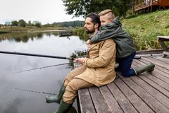 Father and son fishing with rods. On wooden pier at lake Royalty Free Stock Photo