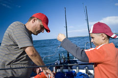 Father and son fishing at sea. A father and son fishing together form a boat at sea (ocean), they are preparing their fishing rods stock photo