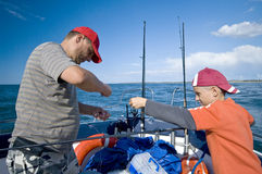Father and son fishing at sea. A father and son fishing together form a boat at sea (ocean), they are preparing their fishing rods Stock Photos