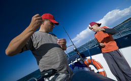 Father and son fishing at sea. A father and son fishing together from a boat at sea (ocean), they are preparing their fishing rods Royalty Free Stock Photos