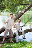 Father with son on fishing, shows size of fish Stock Photo