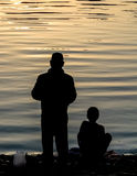 Father and Son Fishing Silhouette. A father and son standing on the lake shore fishing silhouettes Stock Image