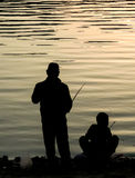 Father and Son Fishing Silhouette. A father and son standing on the lake shore fishing silhouettes Stock Photos