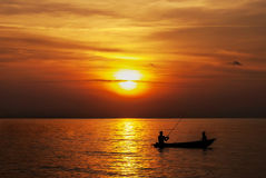Father And Son Fishing While Sunset Hour. Father fishing with his son on boat during sunset hour Royalty Free Stock Photos