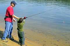 Father and son fishing. A father teaching his son how to fish on a river at the Morrow Mountain State Park Stock Photography