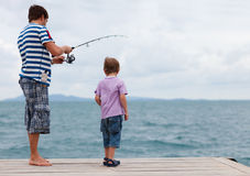 Father and son fishing together. Young father and his son fishing together from wooden jetty Stock Photos