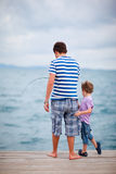 Father and son fishing together. Young father and his son fishing together from wooden jetty Royalty Free Stock Images
