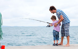 Father and son fishing together. Young father and his son fishing together from wooden jetty Stock Image