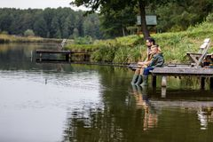 Father and son fishing together. With rods on wooden pier at lake Stock Images