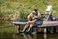 Father and son fishing together. With rods on wooden pier at lake Stock Photos