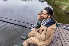 Father and son fishing together. With rods on wooden pier at lake Stock Image