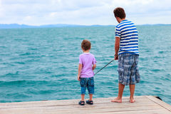 Father and son fishing together. Father and his little son fishing together from wooden jetty stock images