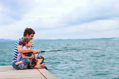 Father and son fishing together. Father and his little son fishing together from wooden jetty stock photography