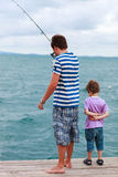 Father and son fishing together. Father and his little son fishing together from wooden jetty royalty free stock photography