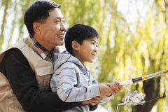 Father and son fishing together at lake Stock Images
