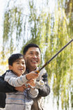 Father and son fishing together at lake Royalty Free Stock Images