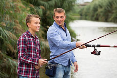 Father and son fishing together on lake. Portrait of joyful father and son fishing together on lake . Focus on boy Stock Images