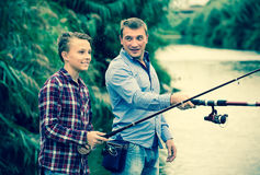 Father and son fishing together on lake. Portrait of joyful father and son fishing together on lake . Focus on boy Stock Image