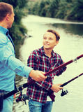 Father and son fishing together on lake Royalty Free Stock Images