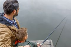 Father and son fishing on pier. Father and son fishing together with rod on wooden pier at lake Royalty Free Stock Images