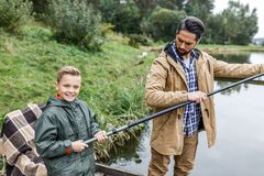 Father and son fishing together. With rod on wooden pier at lake Royalty Free Stock Images