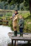 Father and son fishing on lake. Father and son fishing together with rods on wooden pier at lake Royalty Free Stock Image