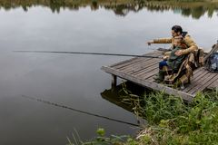 Father and son fishing with rods. Father and son fishing together with rods on wooden pier at lake Royalty Free Stock Photos