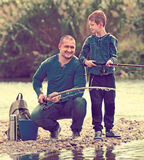 Father and son fishing in wild river Stock Photos