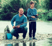 Father and son fishing in wild river Royalty Free Stock Image