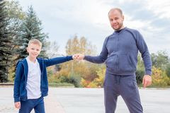 Father and son fist bump while walking in a park stock image
