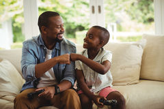 Father and son fist bumping while playing video game. At home stock image