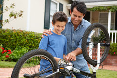 Father and son fixing bike Stock Images