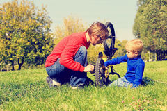Father and son fixing bike outdoors Royalty Free Stock Photography