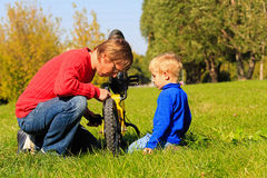 Father and son fixing bike outdoors Stock Photography