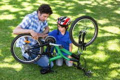 Father and son fixing the bike Royalty Free Stock Photos