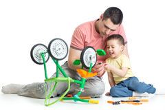 Father and son fixing children bicycle together Stock Photos