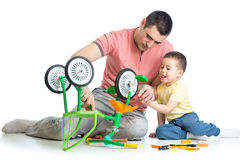 Father and son fixing repairing bicycle wheel Stock Photos