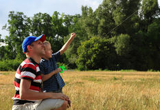 Father and son flies a kite in the sky Royalty Free Stock Image