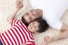 Father and son on floor with heads together Stock Photos