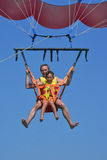 Father and son fly on a parachute over the sea Stock Photo