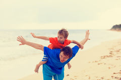 Father and son flying at the beach. Family fun Royalty Free Stock Photos
