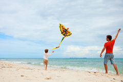 Father and son flying kite. Young father and his son running with kite on the beach stock photos