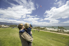 Father and son flying a kite. In a deep blue sky on April 15, 2007, at the Santa Barbara Kite Festival, Santa Barbara City College, overlooking Pacific Ocean Royalty Free Stock Image
