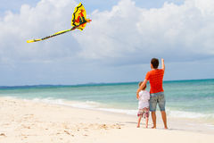 Father and son flying kite on beach Royalty Free Stock Images