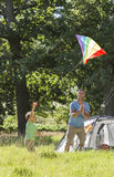 Father And Son Flying Kite Camping Holiday In Countryside Stock Photos